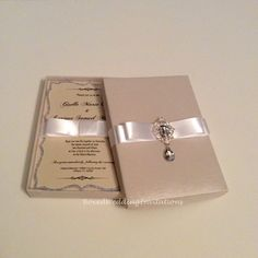 ✨So sparkling!!! Ivory silk box adorned with White satin ribbon and Dangling Crystal brooch. Glitter Invitation Card✨    See more at www.boxedweddinginvitations.com  #wedding #invitations #bride