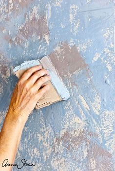Annie Sloan painted this wall with extreme texture using Chalk Paint® in Duck Egg Blue, Old Ochre, Louis Blue, Old White and Coco. She used a sheet of cardboard to apply the paint in textured layers. The finished look is vintage and old.