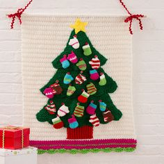 "Christmas Tree Wall Hanging - (free pattern) - ""Use this wonderful decoration as an advent calendar. We've shown it with 12 mittens and 12 stockings that can be filled with goodies to enjoy each December day leading up to Christmas. This fun crochet project will be displayed year after year as part of your family tradition!"""