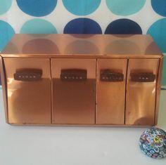 Description: This 1960s mid century modern style metal canister box would be an amazing addition to any kitchen. The copper color and simple design are an eye catching combination. This canister box, made by Lincoln Beautyware, can sit on the counter or be mounted on the wall using the screw holes in the back panel. The handles are wood and labeled Flour, Sugar, Coffee, annd Tea. The four individual canisters are metal on the inside and have a lid to help keep the contents fresh.  Condition…