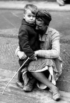 A German woman sobs and cradles her defiant-looking son after she returns to her residence, fleeing an Allied air raid, only to discover her home has been destroyed.