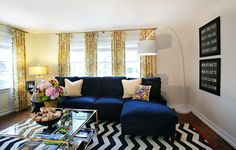 blue sofa like the yellow curtains, white wall, and black accents