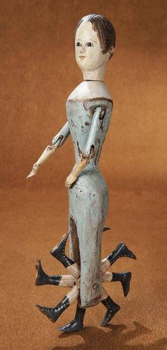 Early nineteenth century walking doll with eight legs that rotate like a wheel.