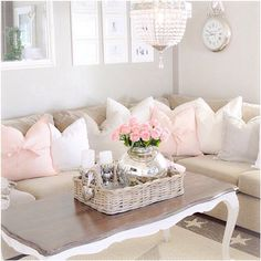 This is such a pretty feminine space with the whites and pinks and that chandelier are so pretty. The wall art behind the couch looks wonderful as well and the coffee table fits the space perfectly. #livingroom #decor #homedecor