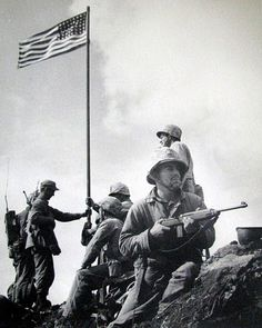 This is Marine photographer Lou Lowery's picture of the first flag-raising. In the foreground holding a carbine is Pfc. James Michels and behind him is Cpl. Charles Lindberg. Lt. Harold Schrier, holds the flag pole on the left, and behind him is Pfc. Louis Chario, hardly visible with a radio on his back. Sgt. Harry Hansen holds the flag pole from the right while Sgt. Ernest Thomas looks on. Photo provided by Dick Honyak