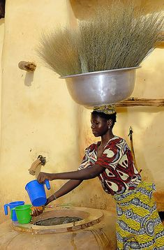 Beautiful, graceful woman in Burkina Faso carrying a large bowl and grasses on her head