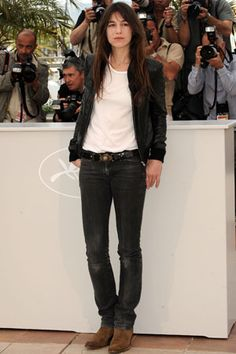 Charlotte Gainsbourg in a white t-shirt, faded black jeans, brown cowboy-ish boots, and a black blazer.