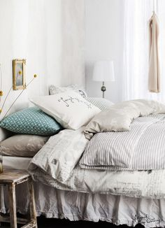 Love the look of a white bedroom. Mix in light shades of grey with a Pop of bright color accent!