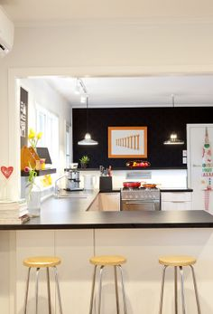 A light, bright kitchen with a black feature wall.