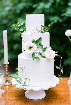A three-tiered white wedding cake decorated with fresh flowers, created by Earth and Sugar.