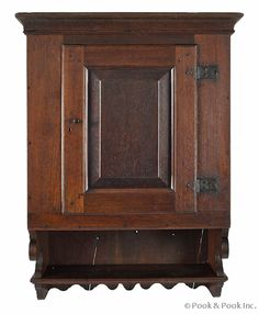 Pennsylvania walnut hanging cupboard, ca. 1770, the molded cornice over a raised panel door with original wrought iron hardware, above an op...