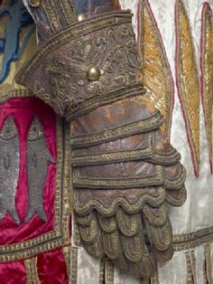 A pair of layered leather gloves decorated with metallic sequins, metal thread and black cord edging. Part of a suit of stage armour worn by the actor Charles Kean in the role of Hotspur in Shakespeare's Henry IV part one. The suit of polished leather on a foundation of red cloth consists of a sleeved jacket, trousers, gauntlets, ankle-boots and damask surcoat with the armorial bearings of Percy of Northumberland - Museum of London
