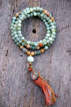 Mala made of 108, 8 mm - 0,315 inch, beautiful jade gemstones and decorated with jade, faceted agate and a nepalese OM (ohm) pendant.    The Mala