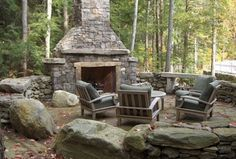 Country Patio with outdoor seating area, exterior stone floors, natural stone retaining wall, stone fireplace...