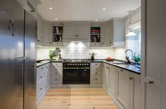 Handpainted kitchen in solid pine from Os Trekultur. The kitchen is tailored to the room after the customer's wishes. Worktop in black granite. Large gas stove from Ilve with brass details.