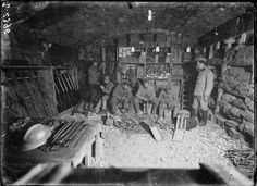 A French quartermasters store at Verdun, 1917. On the table can be seen Hotchkiss clips, with the soldiers sitting putting rounds into machine gun ammunition belts.