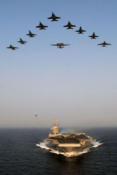 Aircraft from Carrier Air Wing (CVW) 7 fly over the Nimitz-class aircraft carrier USS Dwight D. Eisenhower (CVN 69)