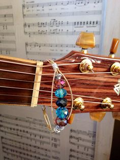 Reused guitar string bracelet adorned with glass faceted beads in aqua, amethyst, and black.  Come visit our shop for more music inspired jewelry, repurposed instruments, playable instruments, and art.  www.MusicAsArtBySarah.etsy.com