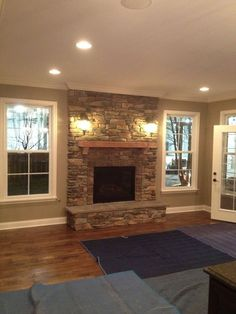 Stone fire place, windows on each side, and put window benches underneath the windows. This WILL replace my big ugly window in my living room someday.