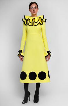 Yellow textured cotton dress with black trim. Upper and lower flounce collar on a stand. Hidden back zip closure. Long sleeves with bows. Without pockets.