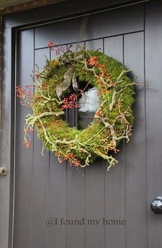 A thick wreath lined with plate moss, branches, rose hips and hangs just over the small window in the door. The ribbon of a beautiful taupe color, with some iron wire aside so he hung what remains messy.