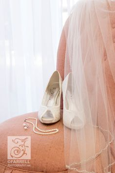 Sacramento wedding photographer, Farrell Photography. Beautiful photograph of brides shoes, jewelry necklace pearls and veil on a pink slipper chair as she gets ready for the wedding.  Farrell Photography is the award winning team of photographer Steve and Stephanie Farrell. Wedding photography, portrait photography, boudoir photography, senior pictures photography, business commercial photography in Northern California, Sacramento Lake Tahoe and destination.