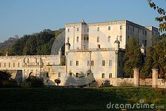 Photo made at the castle Catajo in the province of Padua in Veneto (Italy). In the picture, made at first autumn afternoon, you see the side of the massive main building and part of the high walls, exposed south of sun, both with a corolla of green leaves of the trees on the right and behind and the blue the sky above.