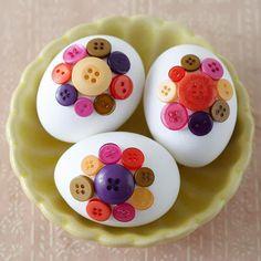 Huevos de Pascua decorados con flores hechas con botones.