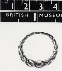 Gilded silver finger-ring; hoop of circular section rods twisted together with beaded wire; narrowing to back; lozenge-shaped thickening at back of hoop.