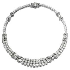 DIAMOND NECKLACE, 1930S. Of articulated graduated design, set with lines of circular-cut diamonds between foliate motif spacers similarly set and accented with single-cut stones, mounted in platinum,