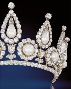 The Rosebery Pearls tiara boasts 13 natural saltwater pearls - six button shaped ones ringed with diamonds and seven pear shaped pearls dangling from tear drop diamond surmounts.