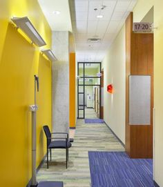 "One of two main ""streets"" leading to exam room clusters within the clinic. Warm, vivid colors and wood and resin paneling accents are continued from the waiting room, with custom signage designed by the architects for wayfinding. Zone doors allow the clinic to scale down in off hours for security and safety. High ceilings throughout the clinic impart spaciousness where windows and skylights have limited impact. Photo: Tom Arban Photography Inc."