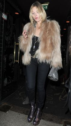 Kate Moss in a fur jacket and an otherwise all black outfit.