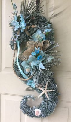 An artificial wreath in the shape of a seahorse and adorned with shells, flowers, nautical rope and a starfish. Almost 2 feet long and a foot wide. Christmas Swags, Blue Christmas, Holiday Wreaths, Coastal Christmas Decor, Rustic Christmas, Christmas Decorations, Primitive Christmas, Christmas Snowman, Horse Head Wreath