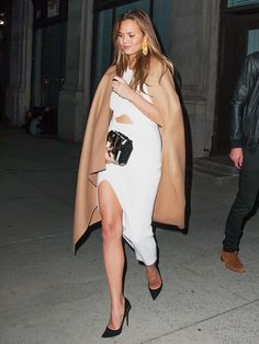 Chrissy Teigen wears a camel coat over a cut-out dress. She pairs the look with oversized earrings and a black clutch.