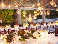 """Idée déco de mariage : les lumignons """"boules de noël"""" dans lesquels on vient insérer de petites bougies artificielles (pas de vraies bougies, hein !) et que l'on suspend à des branches elles-mêmes suspendues au-dessus de la table des mariés. Magnifique sous un chapiteau transparent en plein air ! Source : Ruffledblog.com - Idée déco de mariage : les lumignons-boules"""