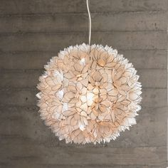 the 'lotus flower chandelier' is assembled with hand-cut capiz shells edged in metal to create blooming flowers that radiate like stained glass.