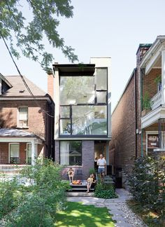 Karen White, David MacNaughtan, and their sons, Griffin and Finlay, hang out on the front deckof their narrow home in Toronto's leafy Roncesvalles neighborhood. A narrow modernist composition of glass panes and purple brick, the house slips like a bookmark between two older buildings, a bright three-story abode on a lot narrower than most suburban driveways.  Photo by Dean Kaufman. Read more about the small house here.