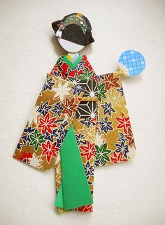 """NFT.  Hand-folded Japanese paper doll (""""ningyo"""") using yuzen washi for kimono and obi; origami paper for kimono lining; gold viscose cord on obi; fan paper cutout; and nail art stickers, yuzen washi strip and fringe for hair décor.  Doll height: 11.2 cm"""