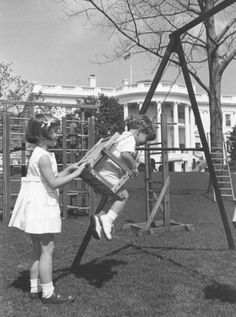 Caroline pushes her brother's swing in the children's playground on the south grounds of the White House.