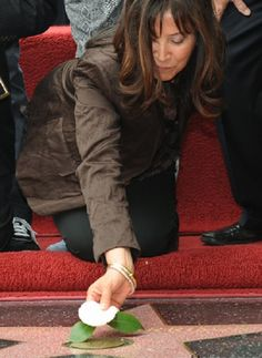 A very touching image of Olivia placing a flower on George's Walk Of Fame star.