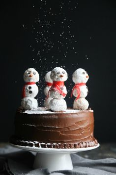 Snowman Cake.. it's just a simple chocolate cake with donut hole snowmen on top! Simple and stunning!! #holidays #christmas #winter