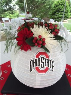 """Ohio State centerpieces for a highschool graduation party. I took the metal piece out of the paper globe and filled a 9.5"""" glass hurricane with glass beads. I bent the two metal pieces at the top of the globe over the rim of the hurricane, filled with water, added an immersible light and added fresh flowers."""