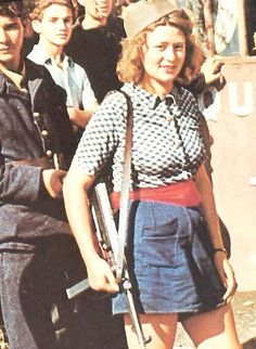 """Parisian-rebel Simone Segouin, also known by her nom de guerre """"Nicole"""", with a German submachine gun MP-40. She killed an unknown number of Germans and captured 25. She was present at the fall of Chartres, on August 23, 1944, and liberation of Paris. She was promoted to lieutenant, and awarded the Croix de guerre."""