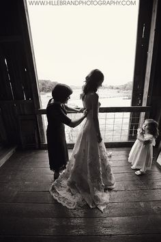 Mom helping daughter get ready on her wedding day. Flower girl watching. In a barn. :)