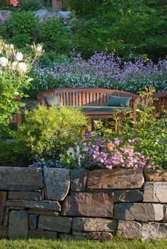 A sun-dappled bench for two overlooks the lawn. Collaborating with stone masons, we created handsome dry-stack retaining walls that provided level areas. We blended warm ledge stone and lichen-covered moss rock in some places for visual variety while in other places we let the elegant stonework act as the focal point. In sunnier areas, we dappled the garden with our client's favorite roses and cutting perennials.