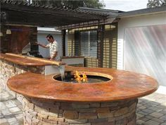 Another round seating area at the end of the outdoor kitchen counter... with a water feature!