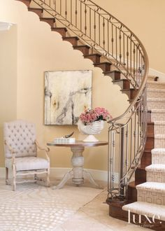 A runner with a geometric pattern and a silk rug in a subtle zebra print add modern zing to the foyer's winding stair-case, travertine floors and traditional weathered-wood furnishings, which include a French mouton chair and a galvanized-steel-topped table.