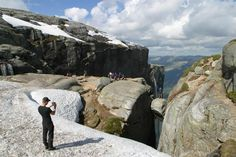 Kjerag - The Majesty of the Lysefjord, Forsand in Ryfylke. At 1084 metres, Kjerag towers above the other peaks along the Lysefjord. It has been traditional to admire this mountain face from the fjord, but in recent years, it has become increasingly popular to walk up the path to the plateau. Most people are happy just to enjoy the view of the Lysefjord from the plateau itself, but for some hikers, the climax of the excursion is to be photographed on the Kjeragbolten, a round rock wedged…