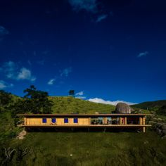 The prefabricated Catuçaba house in Brazil is elevated on stilts and fronted by floor-to-ceiling glazing that offers views out to its remote setting in a rugged, agricultural landscape.